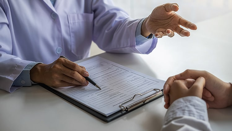 doctor talking with patient over clipboard